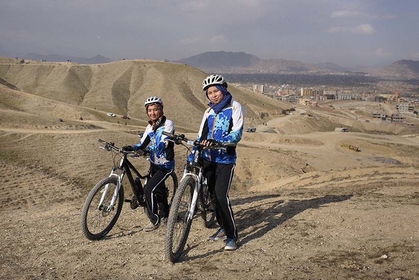 L to R. Zakia Mohammadi (21) and Zahra Naarin (24) with their mountain bikes on a hilly range on the outskirts of Kabul. The two girls travelled from Bamiyan, in central Afghanistan, to Kabul to be interviewed and photographed. (Photograph by Andrew Quilty)