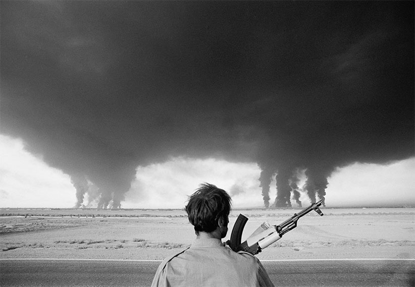 September 1980, Abadan, Iran --- An Iraqi soldier watches as the Iranian Abadan refinery, located near the Iraqi border, burns. The Abadan oil refinery was under constant fire from the Iraqi air force during the Iran-Iraq conflict. (Henri Bureau/Sygma/Corbis)