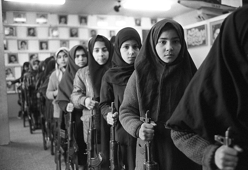 Tehran, Iran: Young schoollgirls in Islamic veils go through arms training as a Basijis (mobilized volunteer forces) while holding AK47 automatic assault rifles and standing in front of pictures of martyrs of Iran-Iraq conflict in a mosque in Tehran, 1988. (Kaveh Kazemi/Getty Images)