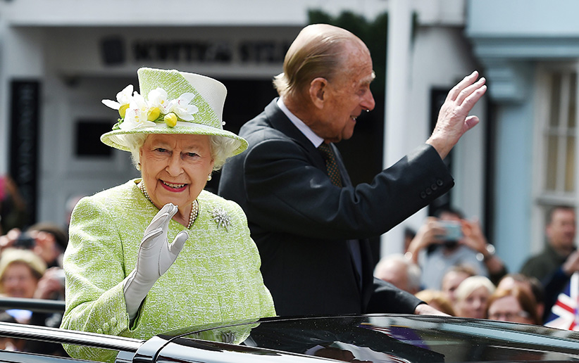 Britain's Queen Elizabeth II and Prince Philip, the Duke of Edinburgh wave to well-wishers during her 90th birthday celebrations in Windsor, Britain, 21 April 2016. Thousands of people turned out to wish Britain's longest serving monarch a happy birthday. (ANDY RAIN/EPA/Getty Images)