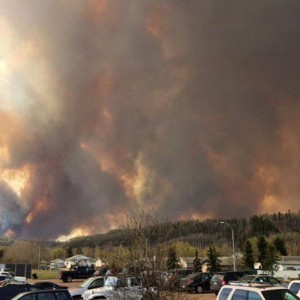 Smoke fills the air near a parking lot in Fort McMurray, Alberta on Tuesday May 3, 2016 in this image provide by radio station CAOS91.1. At least half of the city of Fort McMurray in northern Alberta was under an evacuation notice Tuesday as a wildfire whipped by winds engulfed homes and sent ash raining down on residents. CP