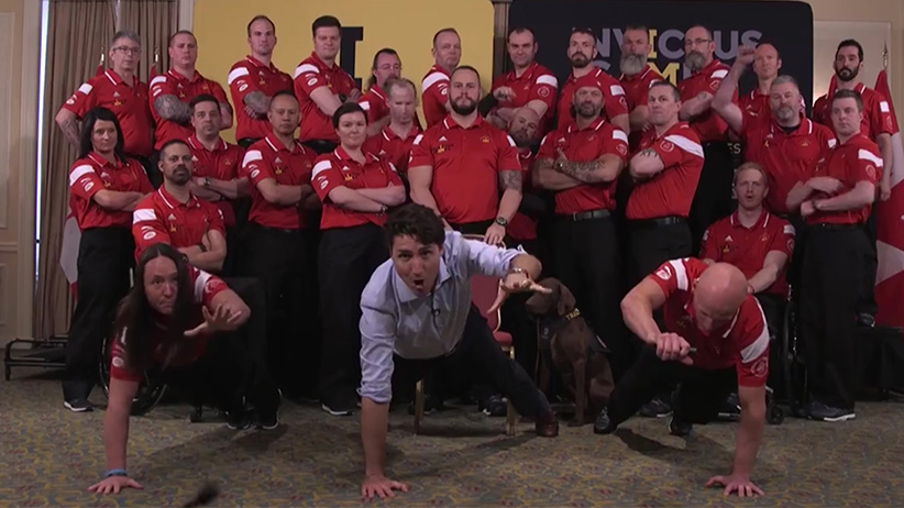 Screen grab of a video where Prime Ministry Justin Trudeau is seen doing one-arm pushups with Invictus Games athletes.