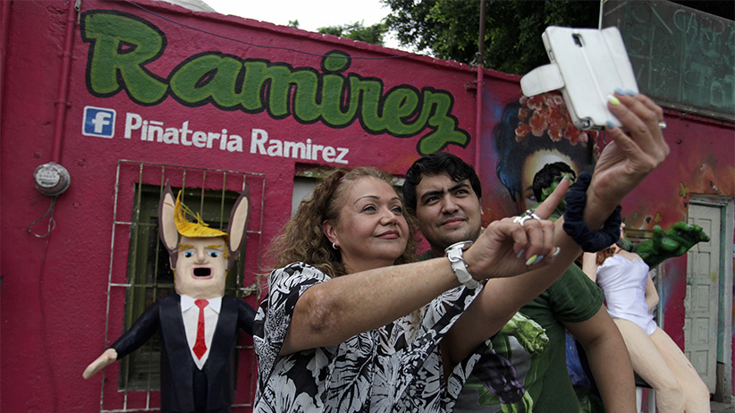 Mexican artisan Dalton Ramirez and a customer pose for a selfie in front of a pinata depicting U.S. Republican presidential candidate Donald Trump outside his workshop in Reynosa, Mexico, June 23, 2015. In the Mexican border city of Reynosa, Dalton Ramirez works at his family's pinata shop where they create a variety of paper mache figures to be filled with treats and broken open with sticks on birthdays and holidays. (Daniel Becerril/Reuters)