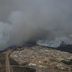 In a photo provided by the Canadian military, smoke from a wildfire billows over a neighborhood of Fort McMurray, Alberta, Canada, May 4, 2016. By Wednesday, about 88,000 people had been evacuated from Fort McMurray, and though no deaths or injuries directly related to the fire have been reported, the oil-industry boom town is still very much in danger. (Mcpl Vanputten/Canadian Armed Forces/The New York Times/Redux)