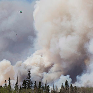 A helicopter battles a wildfire in Fort McMurray Alta, on Wednesday May 4, 2016. The wildfire has already torched 1,600 structures in the evacuated oil hub of Fort McMurray and is poised to renew its attack in another day of scorching heat and strong winds. (Jason franson/CP)