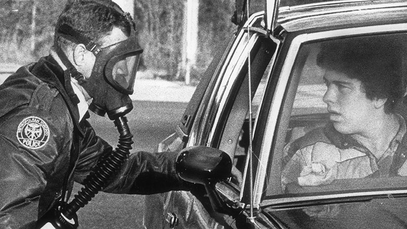 On Nov. 14, 1979, three days after a massive train derailment forced the evacuation of 250,000 residents of Mississauga and Oakville, Metro Toronto Police Constable David McKinlay, wearing a gas mask, stops motorist at Highway 10 and Pinetree Way to explain why access is prohibited. At midnight Saturday, Nov 11, 1979, a spectacular derailment of a CP Rail freight train and subsequent explosion of a propance car resulted in a highly toxic chlorine gas leak from a ruptured tanker car. (Tibor Kolley/The Globe and Mail)