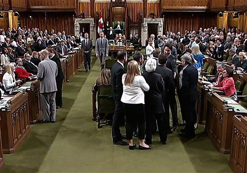 Canadian Prime Minister Justin Trudeau, face towards the camera left of centre of the frame, is shown near Opposition whip Gordon Brown in the House of Commons in Ottawa on Wednesday May 18, 2016. Footage from the Commons television feed shows Trudeau wading into a clutch of MPs, mostly New Democrats, and pulling Opposition whip Gordon Brown through the crowd in order to get a vote started. (CP)
