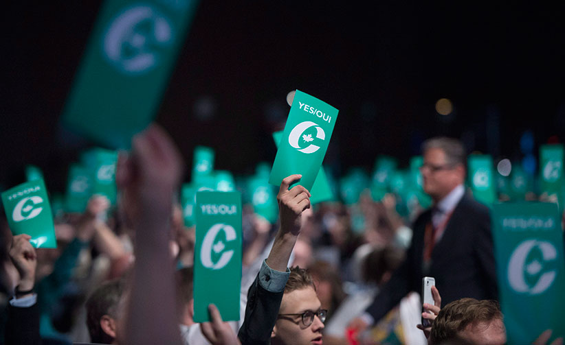 Delegates raise their yes vote cards to change the wording of the traditional definition of marriage in the conservative policies at the Conservative Party of Canada convention in Vancouver, Saturday, May 28, 2016. (Jonathan Hayward/CP)