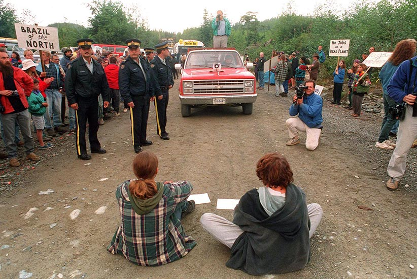 Two protestors block logging trucks to Clayoquot valley as police prepare to move in near Tofino July 1993. Eleven were arrested bringing to the total number of arrests to over 140 since the blockade began July 5. (Chuck Stoody/CP)