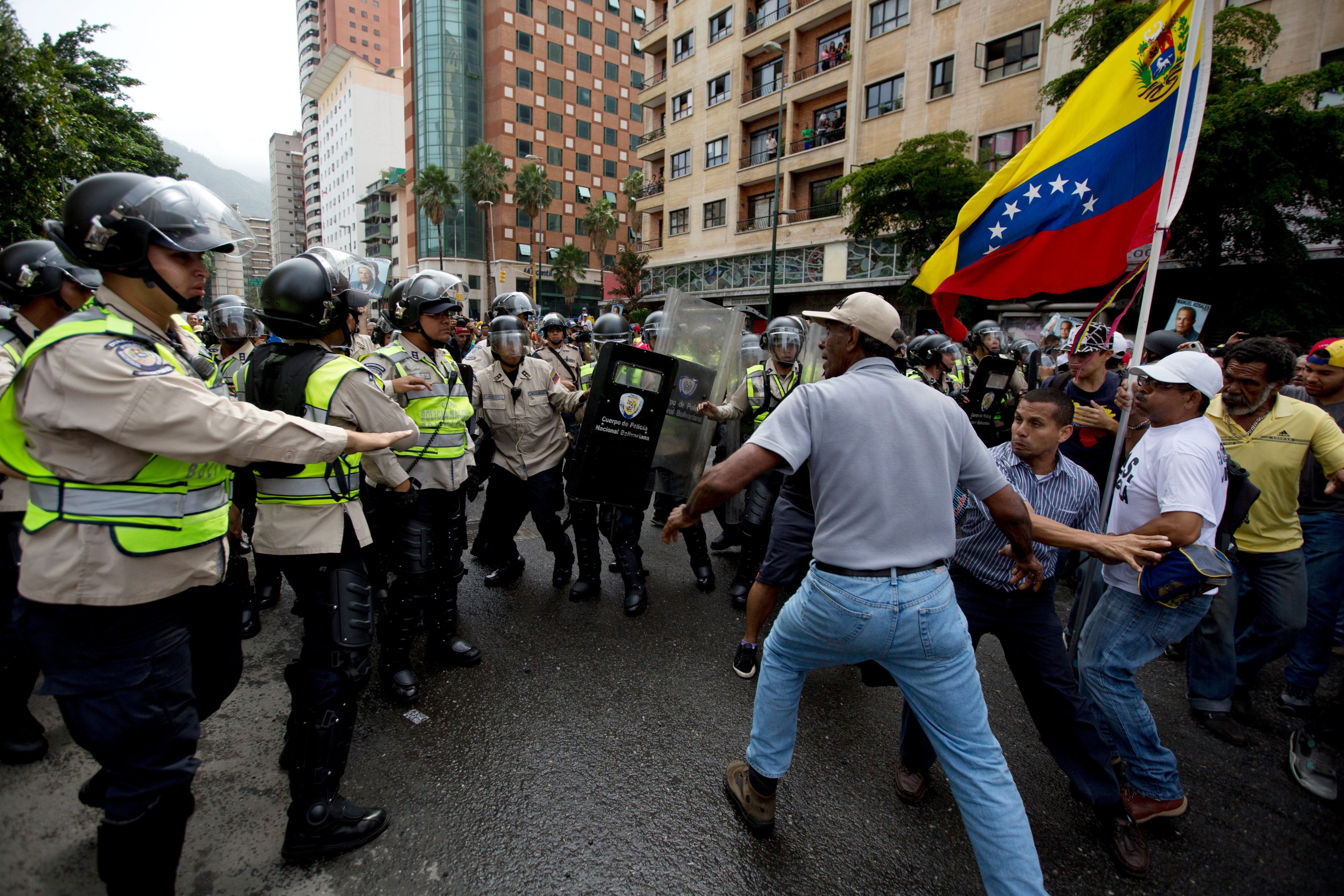 Anti-government demonstrators try to break through a barrier of Bolivarian National Police in an