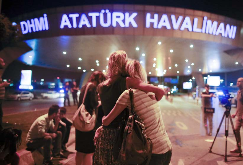 Safety Passengers comfort each other after being evacuated from Istanbul's Ataturk airport, hit by multiple suicide bombers (Emrah Gurel/AP)