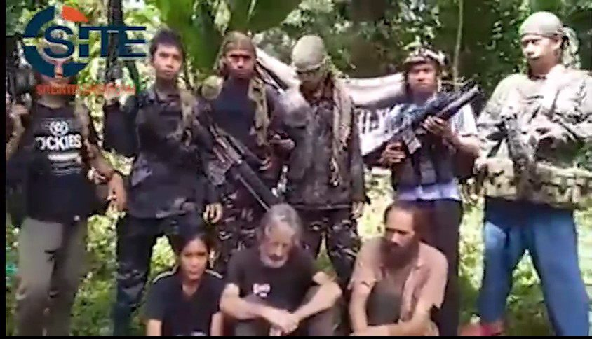 Philippine militants claiming to belong to Abu Sayyaf are seen holding hostages, from left to right, Filipina Marites Flor, Canadian Robert Hall, and Norwegian Kjartan Sekkingstad, in a still frame made from a militant video accessed by the U.S.-based SITE Intelligence Group. THE CANADIAN PRESS/HO-SITE Intelligence Group