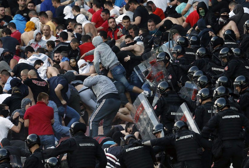 FILE - In this Saturday, April 16, 2016 file photo, Serbian riot police officers clash with Red Star soccer fans during a Serbian National soccer league match between Red Star and Partizan, in Belgrade. Hooliganism is making a comeback, and the timing could be bad with four high-risk matches in the first week of the European Championship in a country where the police force is already under huge strain. (AP Photo/Darko Vojinovic, File)