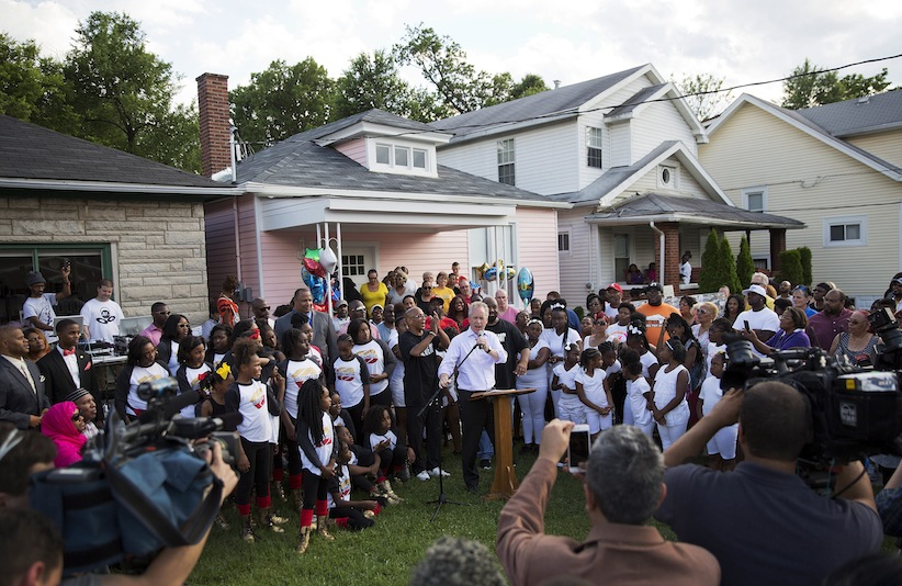 Louisville mayor Greg Fischer speaks at a community memorial service to Muhammad Ali outside his childhood home, rear centre, Monday, June 6, 2016, in Louisville, Ky. (AP Photo/David Goldman)