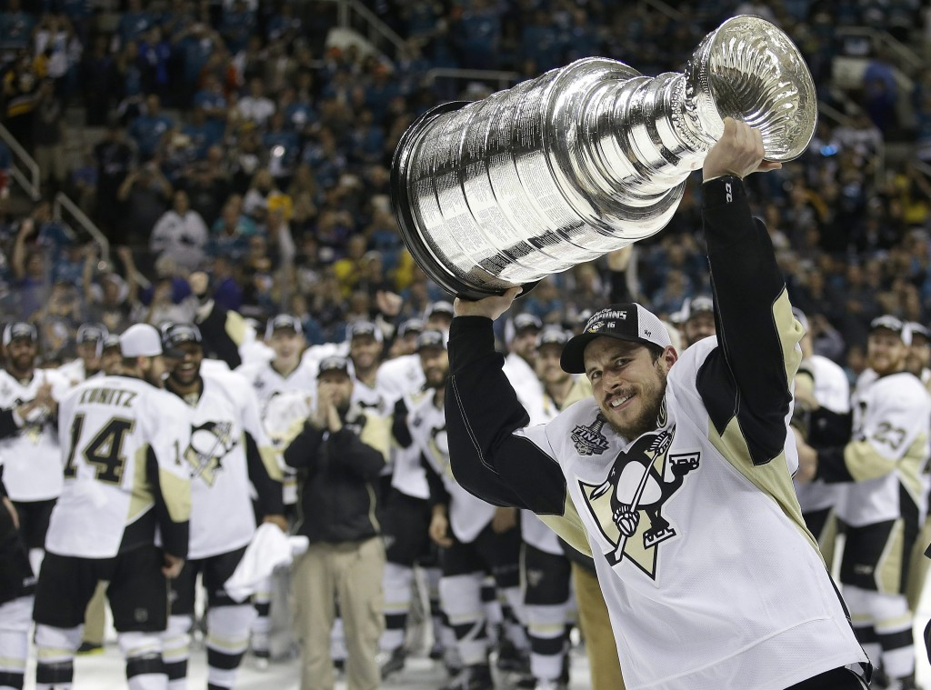 Pittsburgh Penguins center Sidney Crosby raises the Stanley Cup after Game 6 of the NHL hockey Stanley Cup Finals against the San Jose Sharks Sunday, June 12, 2016, in San Jose, Calif. The Pittsburgh Penguins won 3-1 to win the series 4-2. (AP Photo/Marcio Jose Sanchez)