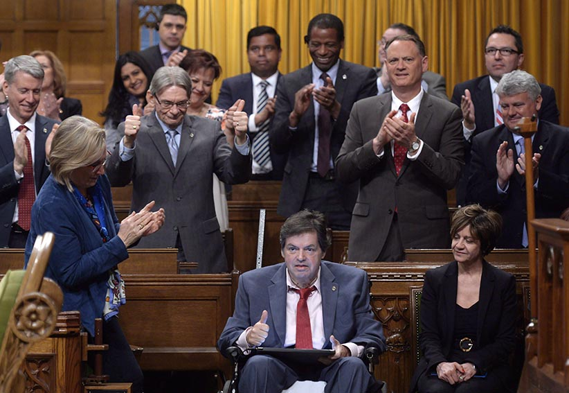 """Ottawa-Vanier MP Mauril Belanger, who lives with ALS (also known as Lou Gherig's disease) uses a tablet with text-to-speech program to defend his proposed changes to neutralize gender in the lyrics to """"O Canada"""" in the House of Commons on Parliament Hill in Ottawa on Friday, May 6, 2016. The lyrics to O Canada will be a hot topic in Ottawa on Tuesday, even though the July 1 fireworks are still a month away.The House of Commons is debating an effort by dying Liberal Mauril Belanger to render the national anthem gender-neutral, by replacing the line in the English version """"in all thy sons command"""" with """"in all of us command."""" (Adrian Wyld/CP)"""