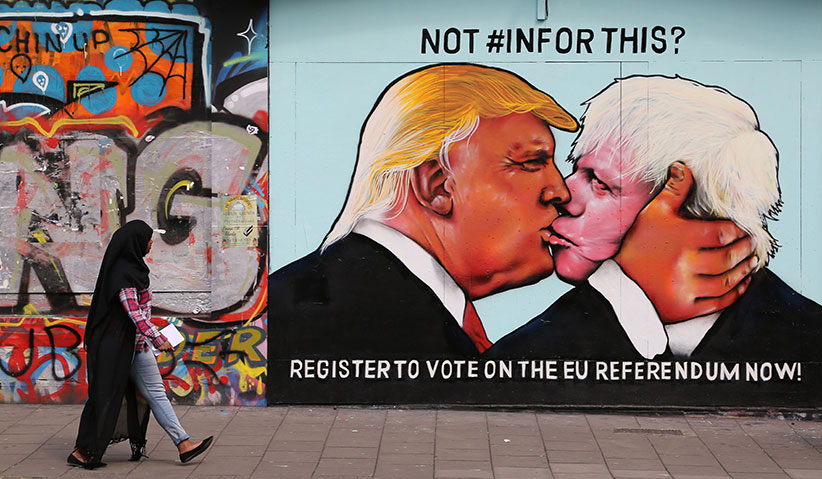 A passer-by views a mural showing likely US Republican presidential nominee Donald Trump (L) kissing the Former Mayor of London and Conservative MP, Boris Johnson, on the side of a building in Bristol, south west England on May 24, 2016. The mural in Bristol, southwest England, was commissioned by We Are Europe, a campaign group which wants Britain to remain in the European Union at the June 23 vote. (Geoff Caddick/AFP/Getty Images)