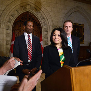 Minister of Democratic Institutions Maryam Monsef is joined by fellow MPs Mark Holland, right, and Greg Fergus as they speak to reporters in the foyer of the house of commons on Parliament Hill in Ottawa on Thursday, June 2, 2016. (Sean Kilpatrick/CP)