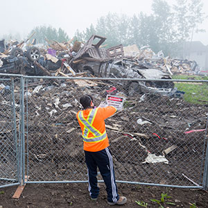 A worker hangs a danger sign on a fence next to burnt homes in the neighbourhood of Prospect Point in Fort McMurray on Thursday, June 02, 2016. Up to 40,000 evacuees are eligible to return to their homes in Fort McMurray, Alta., today, but officials say they expect only about half that number will actually arrive. (Photograph by Chris Bolin)