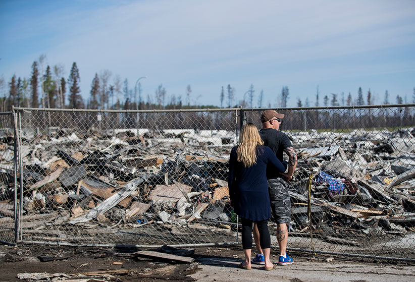 Scott and Samantha Borowsky survey the damage of their neighbourhood in Prospect Point in Fort McMurray on Thursday, June 02, 2016. The couple who lived at 121 Siltstone Place lost their home in the fires. (Photograph by Chris Bolin)