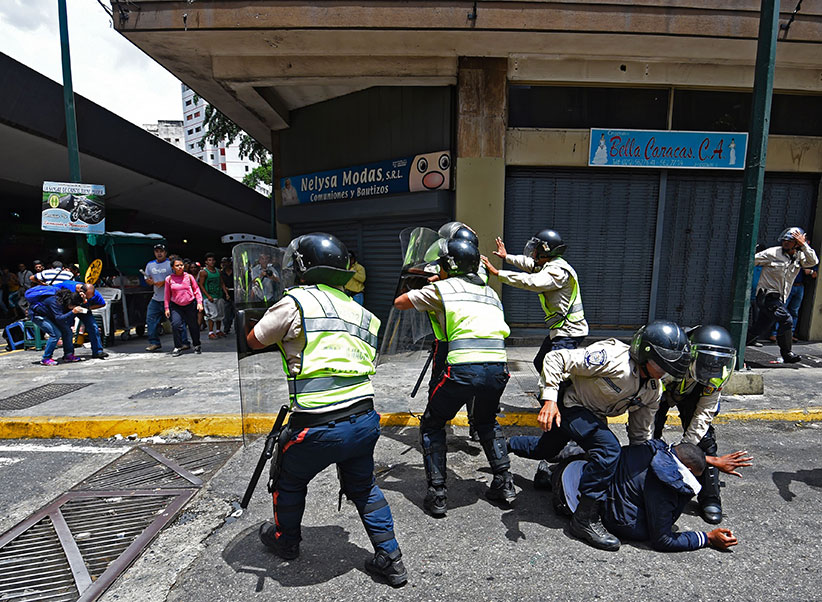 Security forces clash with people trying to reach Miraflores presidential palace to protest against the severe food and medicine shortages, in Caracas on June 2, 2016. Venezuelans face long lines at supermarkets tightly guarded by nervous soldiers, bare shelves and soaring prices inside, a dysfunctional health care system short on basic medications and supplies, daily power cuts of four hours across most of the country, and a government that only operates two days a week to save electricity. (Juan Barreto/AFP/Getty Images)