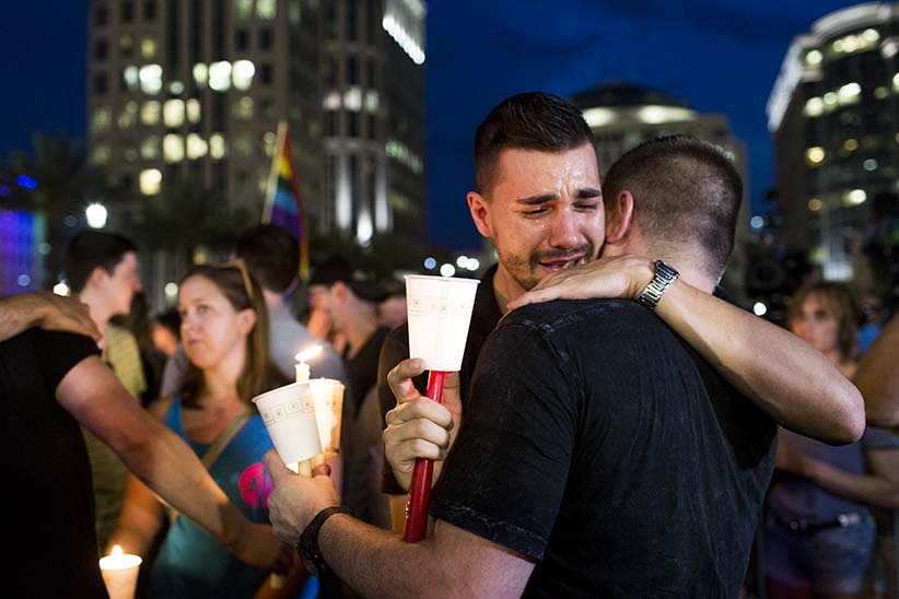 Mourners comfort eachother at a vigil in ORlando on June 13th, 2016. (Photograph by Roger Kisby/Redux)