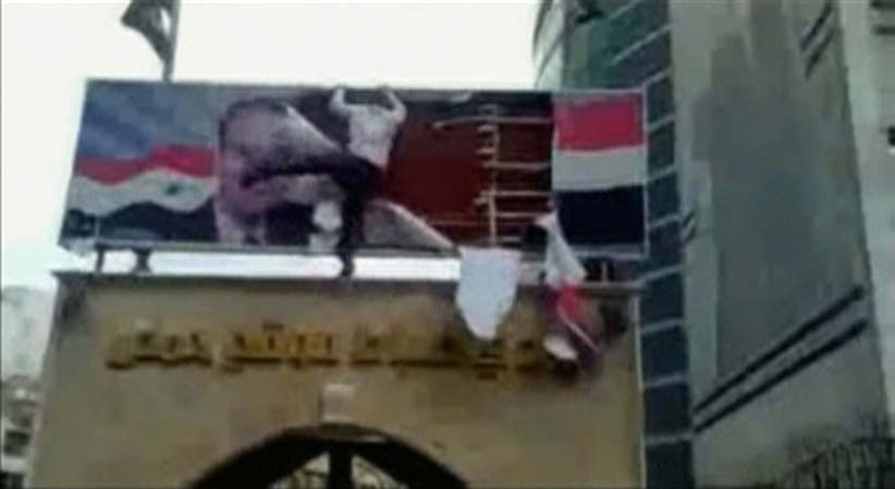 This still image taken from amateur video shows a protester defacing a giant poster of late Syria President Hafez al-Assad in Homs March 25, 2011. Syrian President Bashar al-Assad was facing the deepest crisis of his 11 years in power after security forces fired on protesters on Friday, adding to a death toll that rights groups have said now numbers in the dozens. Footage taken March 25, 2011. There was no way to independently verify the contents of the videos. (Reuters)