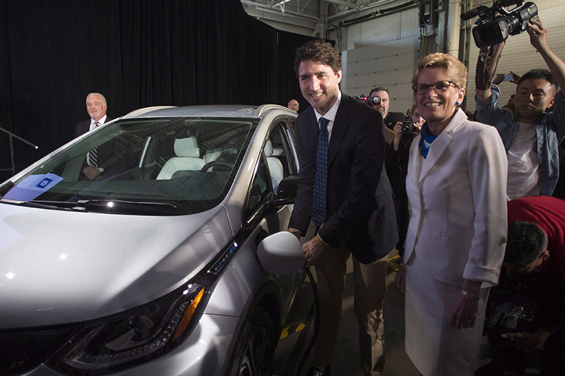 Prime Minister Justin Trudeau, left, and Ontario Premier Kathleen Wynne pose as they plug in a 2017 Chevrolet Volt electric vehicle before making an announcement at the General Motors plant in Oshawa, Ont., on Friday, June 10, 2016. (Chris Young/CP)