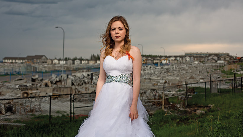 Sarah Barrett poses in her prom dress outside her burned out neighbourhood in For McMurray, Alberta on Monday, June 6, 2016. Photograph by Amber Bracken