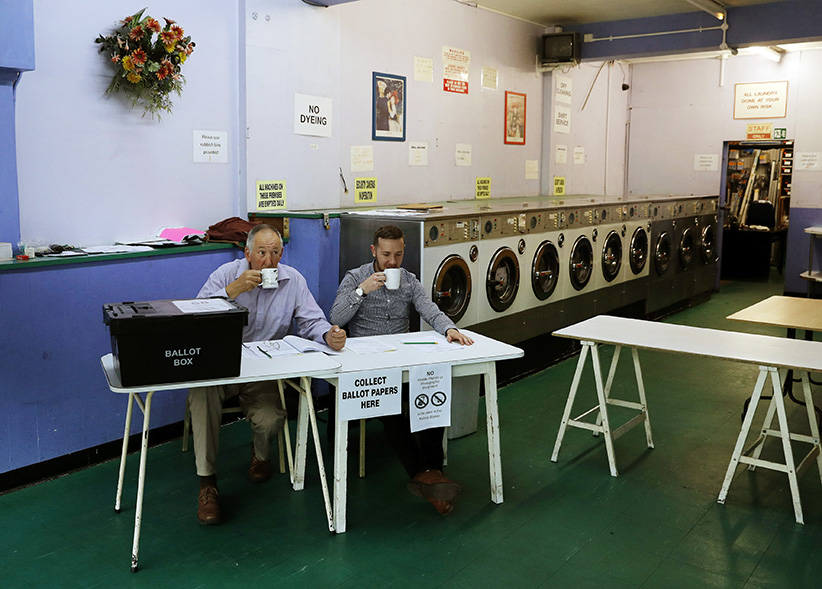 A presiding officer (L) and poll clerk (C) drink a cup of tea while waiting for early morning voters at a polling station set up in a launderette in Headington outside Oxford on June 23, 2016. Millions of Britons began voting today in a bitterly-fought, knife-edge referendum that could tear up the island nation's EU membership and spark the greatest emergency of the bloc's 60-year history. (ADRIAN DENNIS/AFP/GETTY IMAGES)