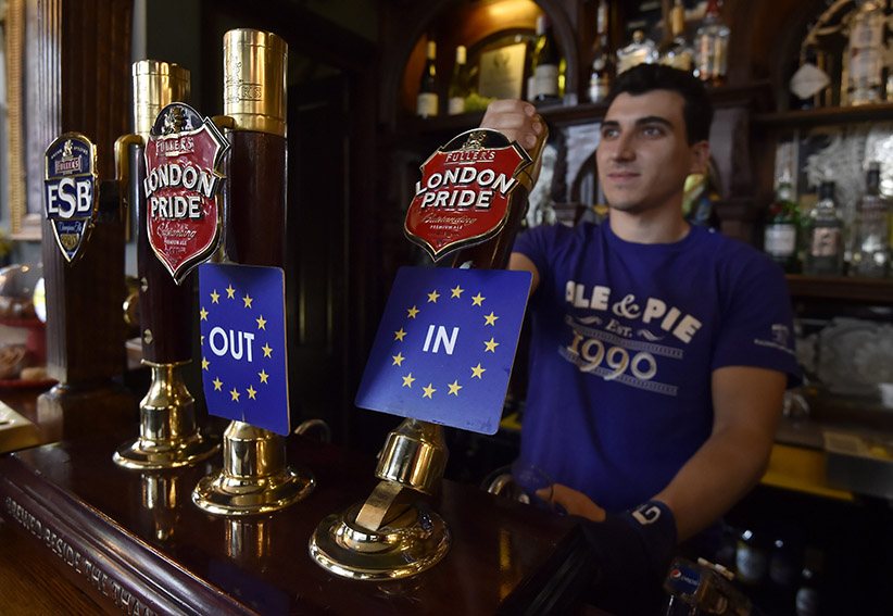A bar tender pulls a pint of beer decorated with EU Referendum beer taps in a pub in central London. (HANNAH MCKAY/EPA/CP)