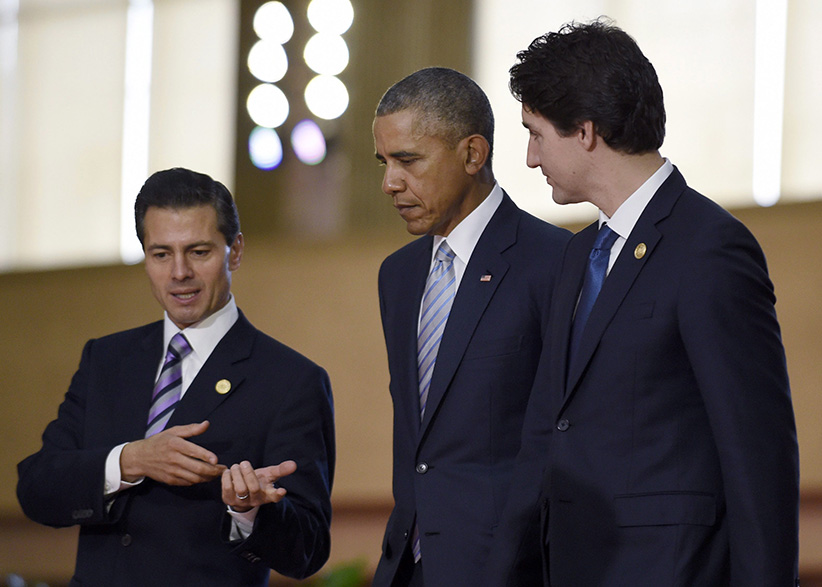President Barack Obama, center, walks with Mexico's President Enrique Pena Nieto, left, Canada's Prime Minister Justin Trudeau, right, as they arrive for a group photo with leaders of the Asia-Pacific Economic Cooperation summit in Manila, Philippines, Thursday, Nov. 19, 2015. (Susan Walsh/AP)