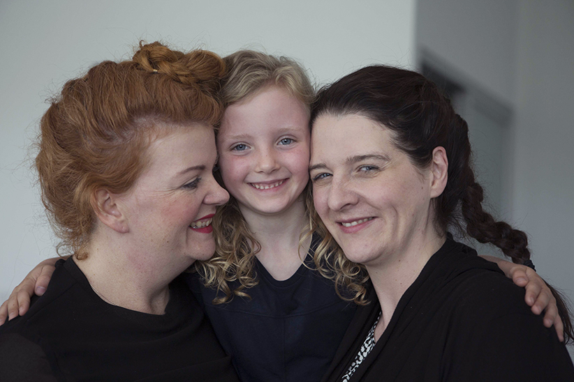 Ruby Mathers (centre), born in 2010, with her two moms. (Photograph by Della Rollins)
