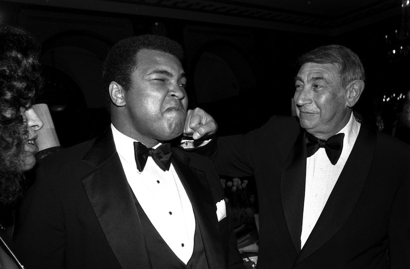 FILE - In this April 13, 1981, file photo, sportscaster Howard Cosell, right, is pictured laying one on the chin of former world heavyweight boxing champ Muhammad Ali during a dinner in New York. Ali, the magnificent heavyweight champion whose fast fists and irrepressible personality transcended sports and captivated the world, has died according to a statement released by his family Friday, June 3, 2016. He was 74. (AP Photo/Richard Drew, File)