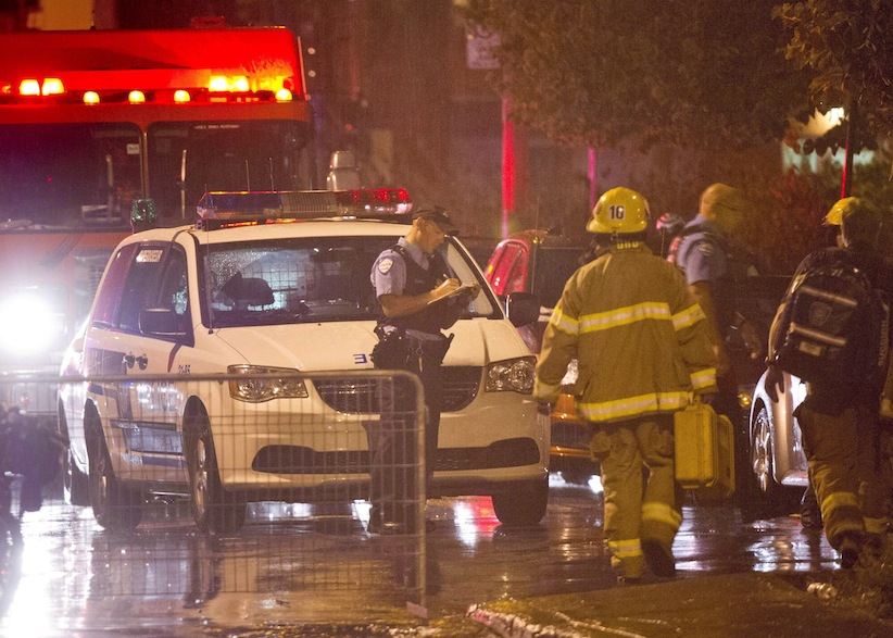 Police and fireman work at the rear of an auditorium where a gunman shot and killed at least one person during the PQ victory rally on September 5, 2012, in Montreal. (THE CANADIAN PRESS/Paul Chiasson)