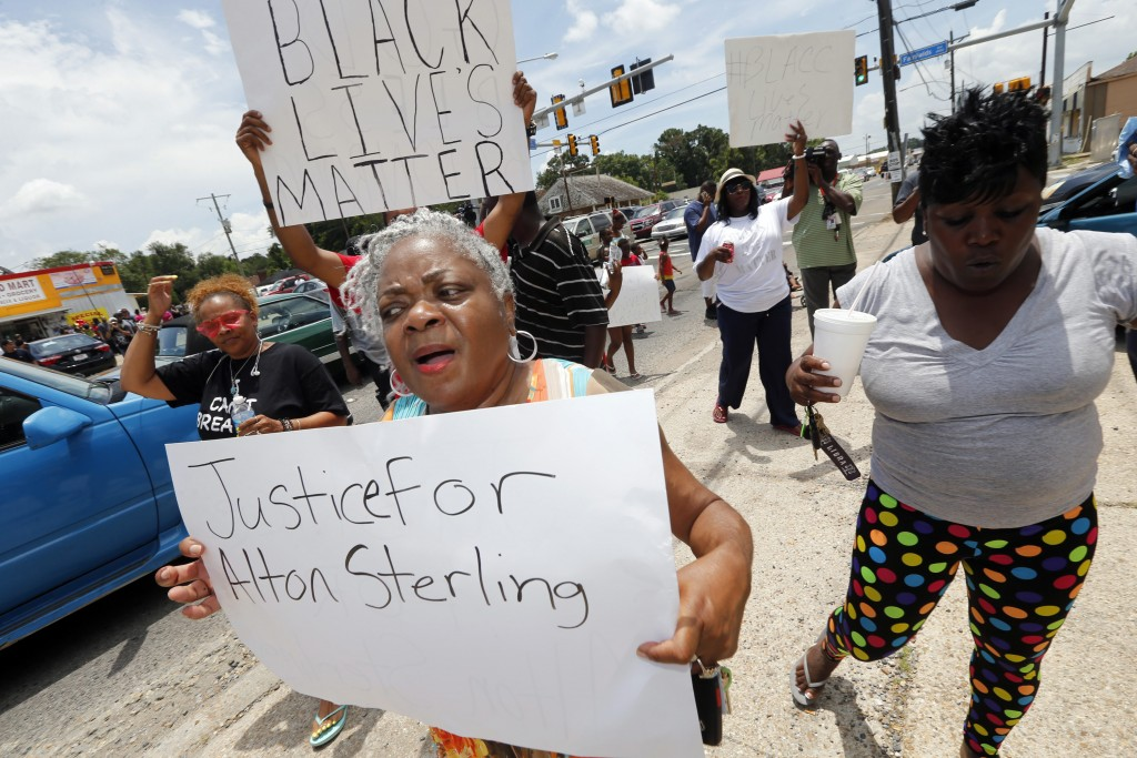 People march outside the Triple S convenience store in Baton Rouge, La., Wednesday, July 6, 2016. Alton Sterling was shot and killed outside the store where he was selling CDs Tuesday by Baton Rouge police. The U.S. Justice Department opened a civil rights investigation Wednesday into the videotaped police killing of Sterling. (AP Photo/Gerald Herbert)