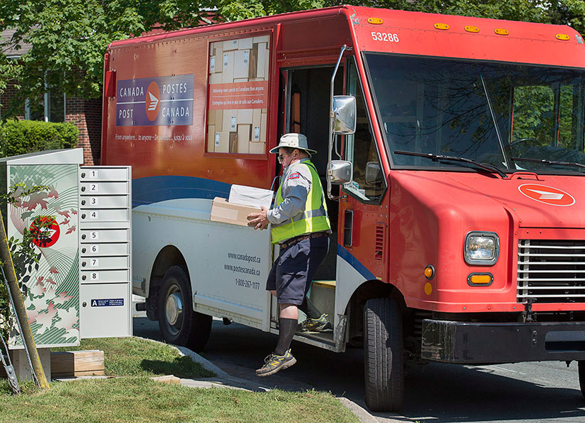 A Canada Post employee fills a community mail box in Dartmouth, N.S. on Thursday, June 30, 2016. (Andrew Vaughan/CP)