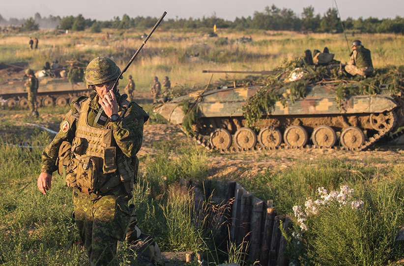 A Canadian soldier sends the signal to begin the simulated attack on a defensive position during a live firing exercise during Operation UNIFIER in Starychi, Ukraine on June 30, 2016. (Joint Task Force Ukraine)