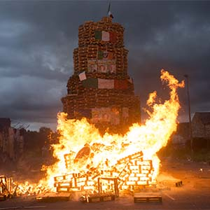 A smaller bonfire is lit before midnight for the children to watch. On the larger bonfire in Bloomfield Walkway bonfire in East Belfast, Irish flags and political posters of Sinn Féin, the main Nationalist party in Northern Ireland, are on the bonfire to be burned. (Photograph by Paul Colangello)