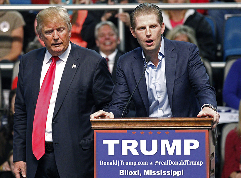 Republican presidential candidate Donald Trump, left, listens as his son Eric Trump speaks during a rally in Biloxi, Miss. (Rogelio V. Solis/AP)