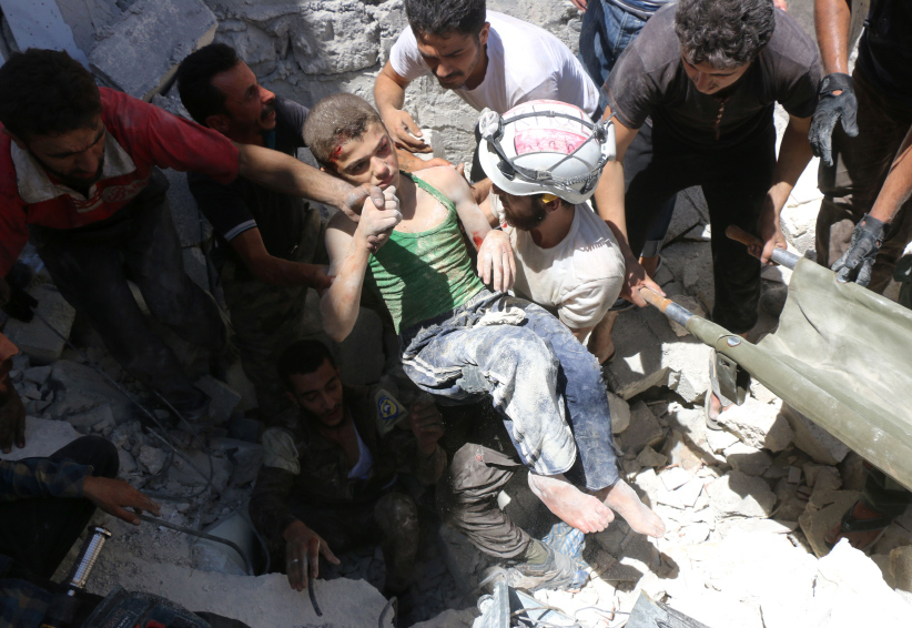 Syrian civil defence volunteers, known as the White Helmets, carry a young boy after they dug him out from under the rubble of buildings destroyed following reported air strikes on the rebel-held neighbourhood of Al-Mashhad in the northern city of Aleppo, on July 25, 2016. Air strikes and barrel bomb attacks killed 16 civilians in rebel-held parts of Aleppo province, with rebel rocket fire onto government areas killing three more, the Britain-based Syrian Observatory for Human Rights said. (Thaer Mohammed/AFP/Getty Images)