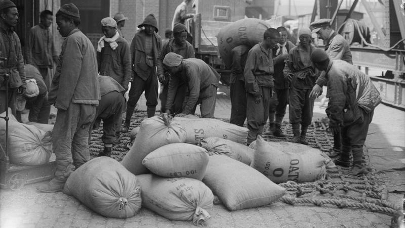 Men of Chinese Labour Corps loading sacks of oats on to a lorry at Boulogne, 12th August 1917. (Lieutenant Ernest Brooks/Imperial War Museums)