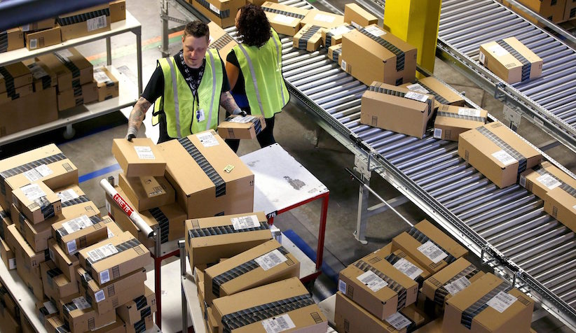 "FILE - In this Monday, Dec. 2, 2013, file photo, Amazon.com employees organize outbound packages at an Amazon.com Fulfillment Center on ""Cyber Monday"" the busiest online shopping day of the holiday season in Phoenix. Amazon announced Wednesday, March 9, 2016, it has finalized an agreement to lease 20 Boeing jets from Air Transport Services Group as it builds out its delivery capabilities. (AP Photo/Ross D. Franklin, File)"