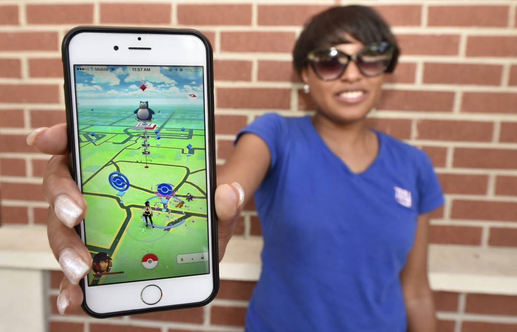 Keyanna Arnett poses for a photo with the Pokémon Go game on her cell phone at Augusta University in Augusta, Ga., Tuesday, July 12, 2016.  (Michael Holahan/The Augusta Chronicle via AP)