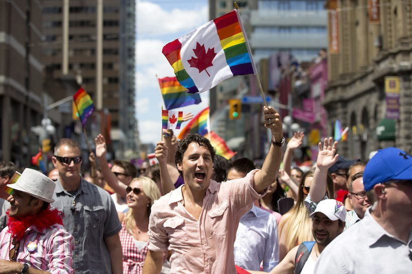 Prime Minister Justin Trudeau waves a flag as he takes part in the annual Pride Parade in Toronto on Sunday, July 3, 2016. THE CANADIAN PRESS/Mark Blinch