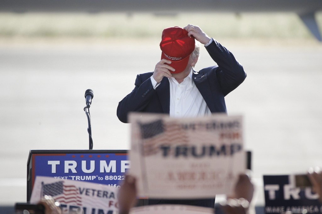 Republican presidential candidate Donald Trump puts on his hat during a rally, Wednesday, June 1, 2016, in Sacramento, Calif. (AP Photo/Jae C. Hong)