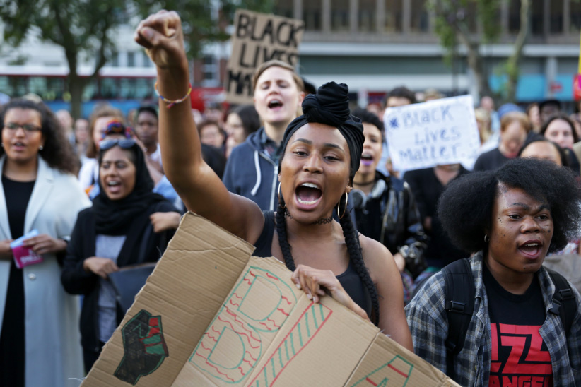 People chant and hold up with placards in Altab Ali Park in east London, as they attend a Black Lives Matter event, on August 5, 2016. (Daniel Leal-Olivas/Getty)