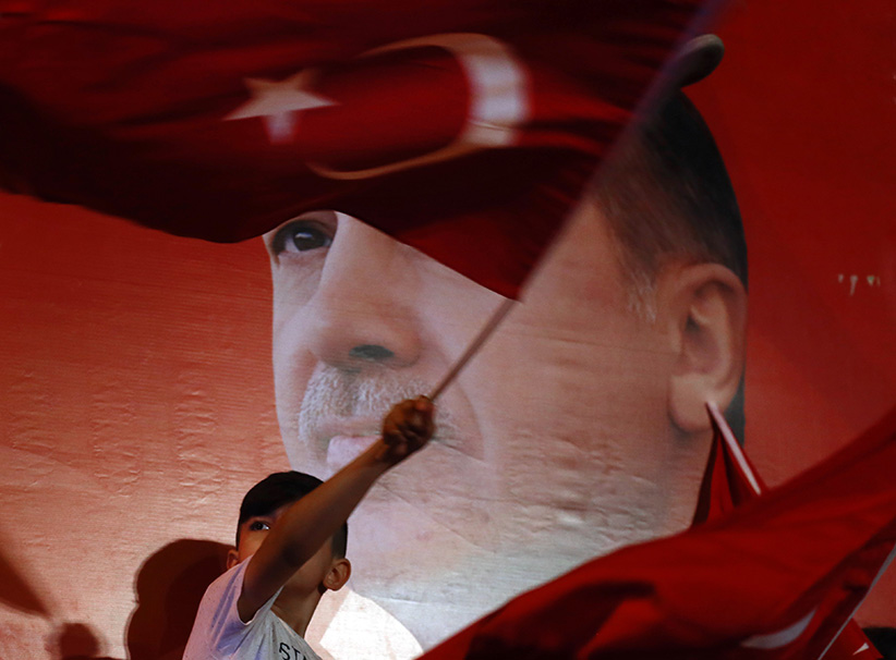 A kid waves Turkish Flag near a poster of Turkish President Recep Tayyip Erdogan in front of Erdogan's Istanbul residence in Kisikli Neighborhood on July 26, 2016. (Abdullah Coskun/Anadolu Agency/Getty Images)