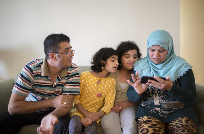 Government sponsored Syrian refugees (from left) Shaher Kattaf, Jihan Kattaf, Nisreen Kattaf and Zahara Hasham at their two-bedroom apartment in Mississauga, Ont. (Photograph by Nick Iwanyshyn)