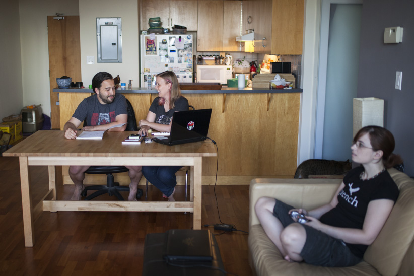 Tabby Rose and Jeff Rose work at the table while roommate Jo Daly plays video games in their shared Toronto condo. (Photograph by Nick Iwanyshyn)